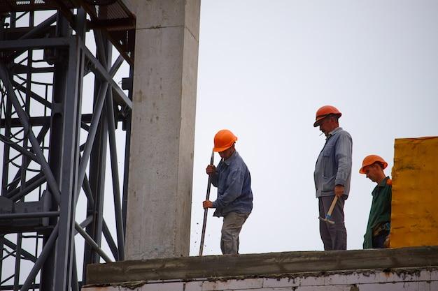 Construtores masculinos trabalham na construção de um edifício de cimento de vários andares