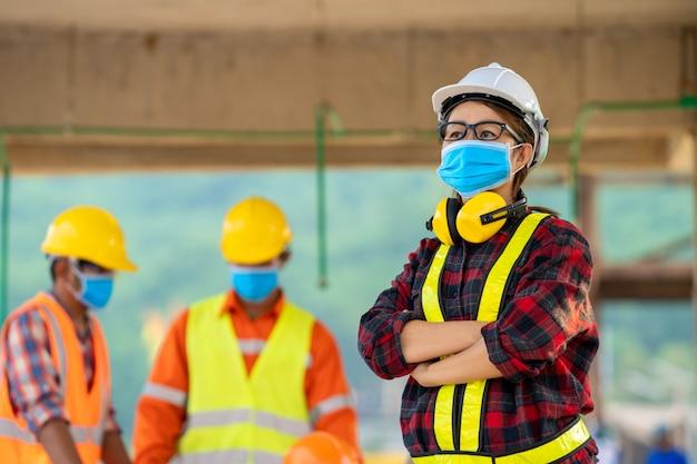 Construtores que vestem o capacete de segurança com o modelo na construção, conceito da construção residencial em construção.