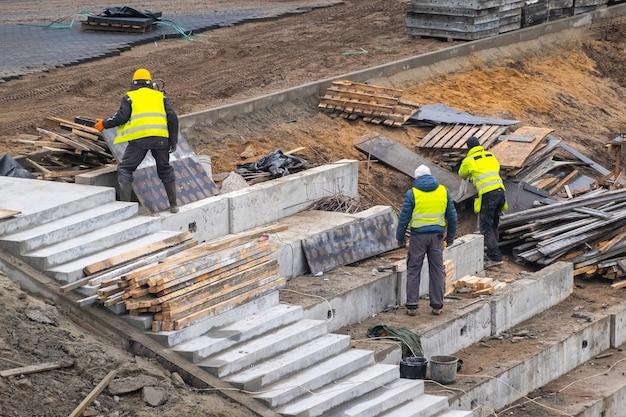 Construtores trabalhando na fundação da construção. homem reforça estrutura de concreto na encosta da colina