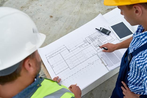 Construtores verificando plantas no local