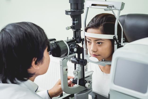 Consulta com um oftalmologista. médico e jovem mulher asiática