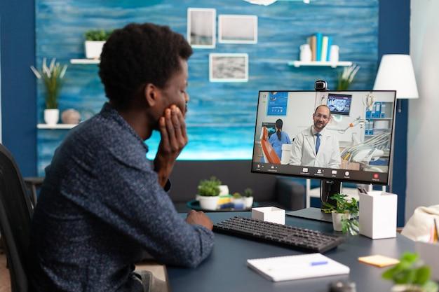 Consulta de saúde de um cara afro-americano falando com um médico usando o aplicativo de videochamada sentado na casa ...
