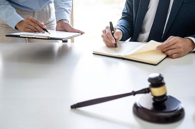 Consulta e conferência de advogados masculinos e empresária profissional a trabalhar e discussão tendo em escritório de advocacia em exercício. conceitos de direito, martelo do juiz com balança de justiça.