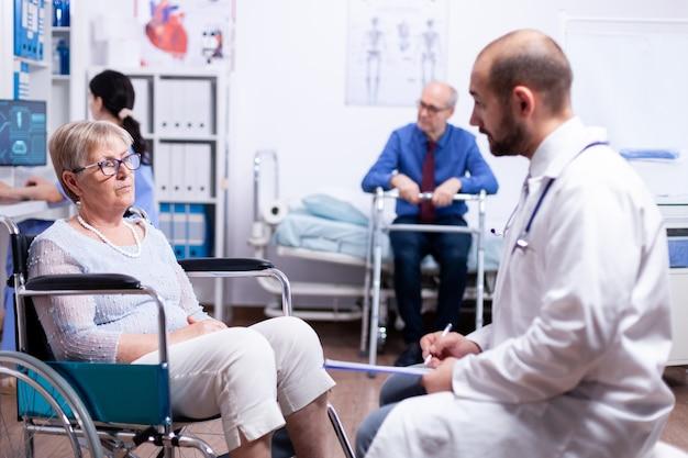 Consulta médica em clínica de recuperação de mulher idosa com deficiência em cadeira de rodas
