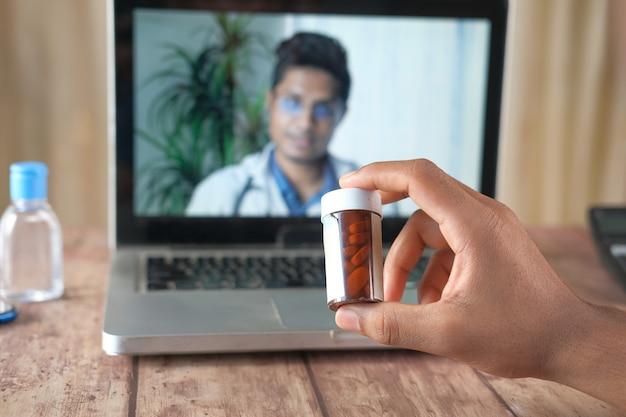 Consulta online com médico no laptop e segurando um recipiente para comprimidos médicos