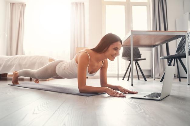 Consulta online. menina morena encantada expressando positividade enquanto olha para o computador durante o treinamento