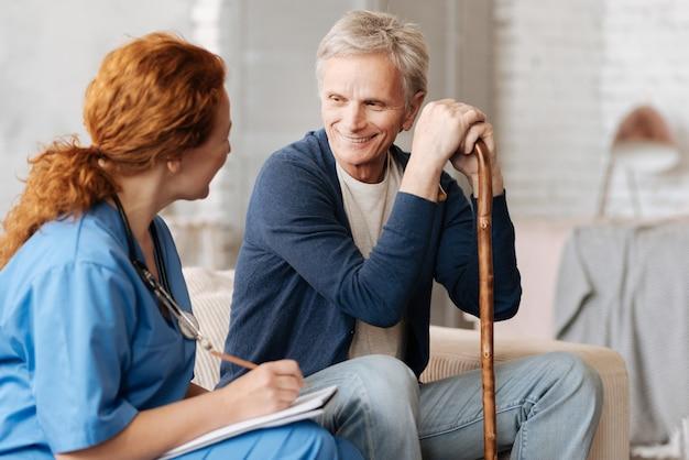 Consulta positiva. médico excelente atencioso perguntando a cavalheiros maduros sobre sua saúde e anotando fatos importantes para analisá-los e prescrever o tratamento