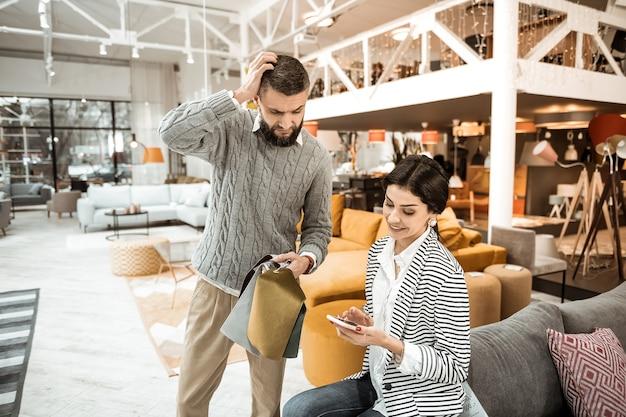 Consultando a esposa. senhora arrumada de cabelos compridos mostrando designs para o marido em um smartphone enquanto visitava uma loja de móveis