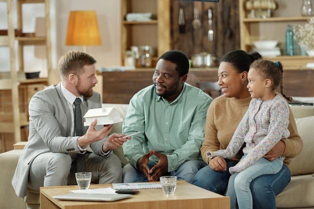 Consultor barbudo e elegante com maquete de casa, consultando casal étnico adulto com filho em um novo imóvel