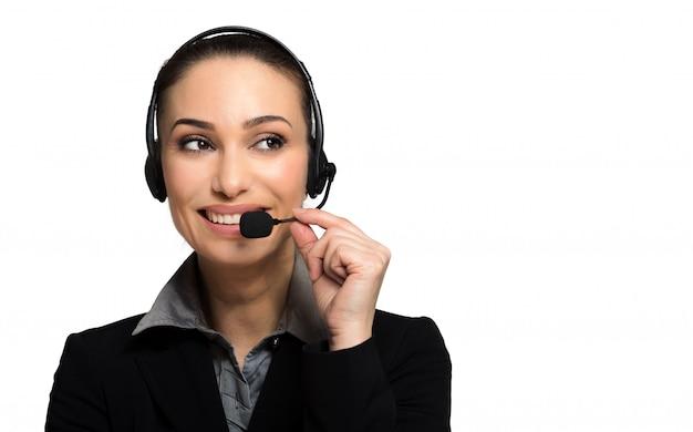 Consultor bonito do call center em fones de ouvido no fundo branco