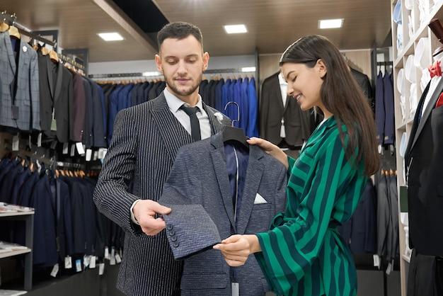 Consultor de cliente e loja olhando e experimentando a jaqueta.