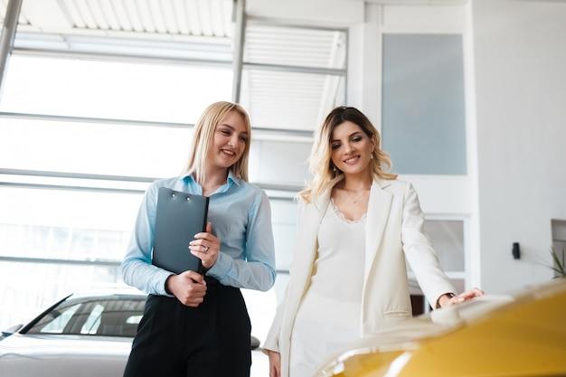 Consultor de concessionária mostra carros para um cliente