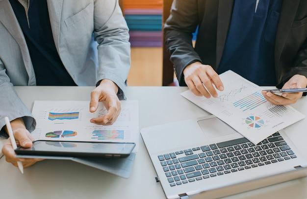 Consultor de investimento de dois empresários analisando relatório financeiro da empresa