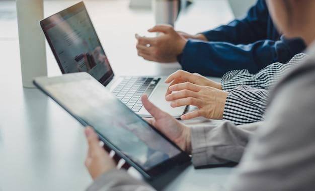 Consultor de investimento de três empresário analisando o relatório financeiro da empresa.