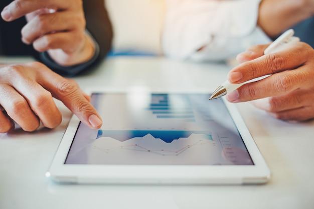 Consultor de investimentos de dois empresários analisando o relatório financeiro da empresa