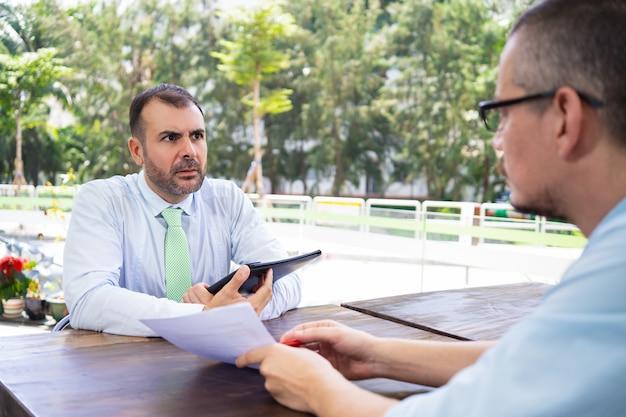 Consultor de negócios explicando documentos para cliente hispânico