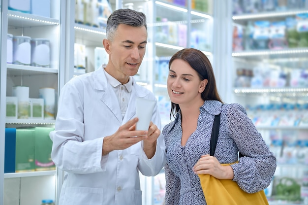 Consultor farmacêutico experiente aconselhando uma cliente