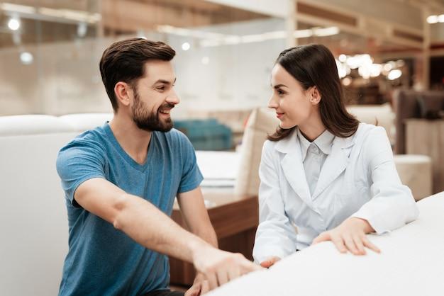 Consultor feminino atraente, ajudando o homem jovem