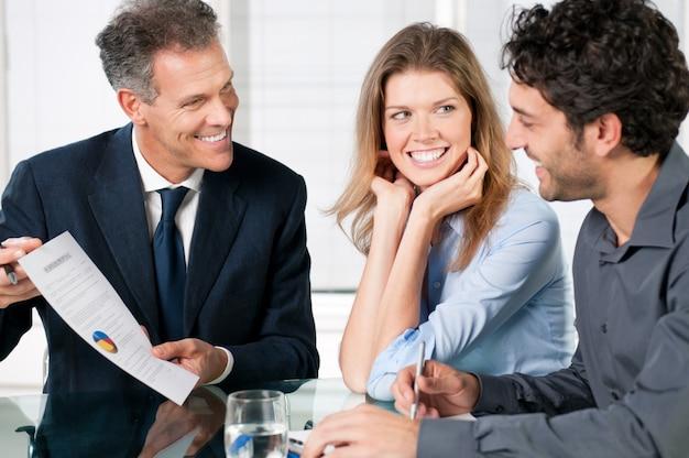 Consultor financeiro apresentando um investimento empresarial a um jovem casal sorridente