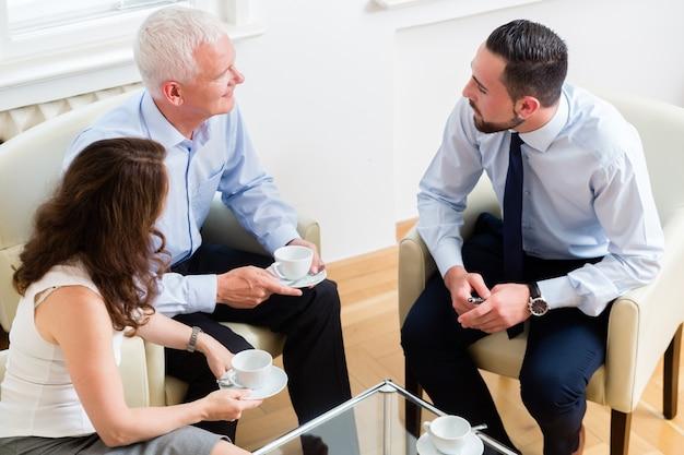 Consultor financeiro assessorando casal em planejamento de aposentadoria em escritório moderno e luminoso