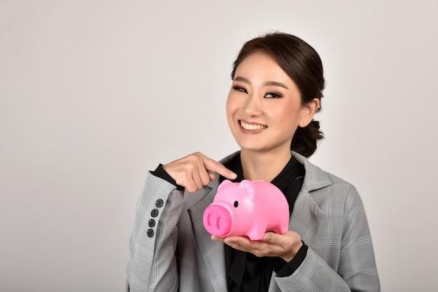 Consultor financeiro, especialista em economia de dinheiro, mulher de negócios asiáticos sorrindo e segurando o cofrinho rosa, riqueza e seguro de planejamento financeiro para investimento.