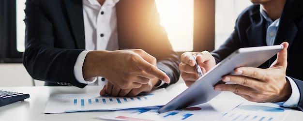 Consultor jurídico e empresário, dois empresários conversando, planejando analisar investimento e marketing em tablet no escritório.