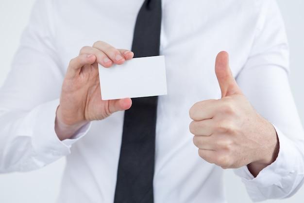 Consultor masculino que mostra o cartão de visita e o thumb-up