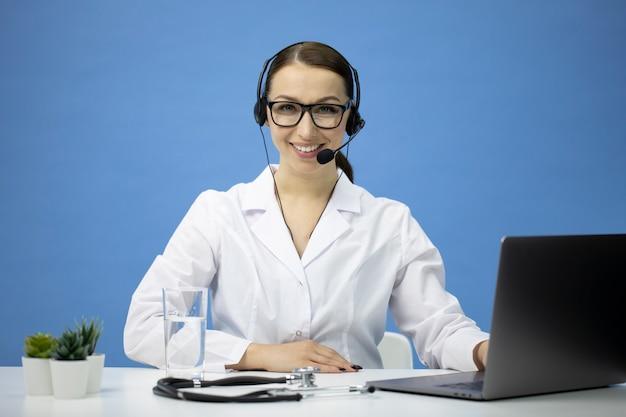 Consultor médico on-line atraente sexy no fone de ouvido olha para a câmera e sorri