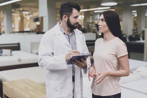 Consultor ortopedista ajuda a menina a escolher um colchão.