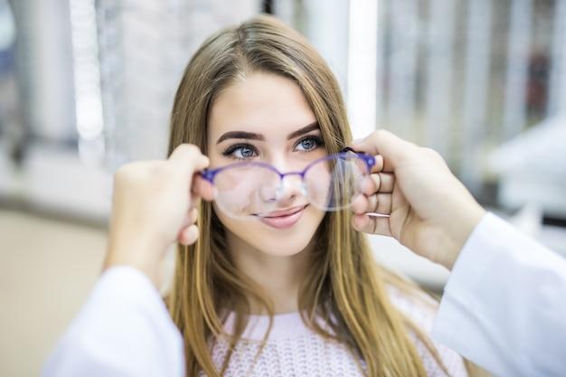 Consultor profissional ajuda seu cliente a escolher óculos médicos em loja moderna