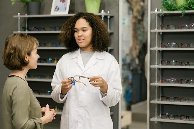 Consultora bonita de jaleco branco mostrando novo modelo de óculos enquanto fala sobre suas características ao cliente