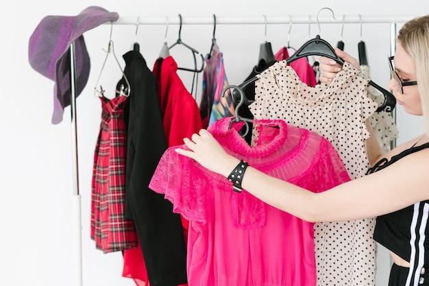 Consultora de estilo pessoal ou estilista de moda escolhendo roupas da moda para seu cliente. mulher segurando dois topos em cabides.