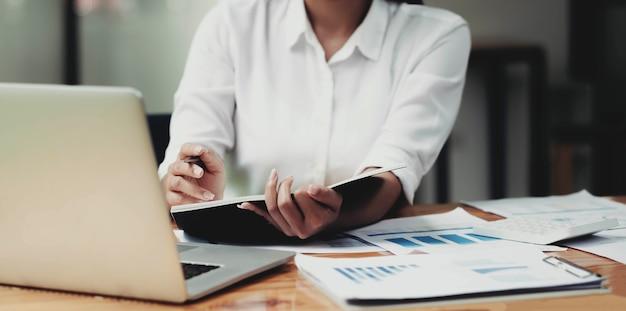 Consultora de investimentos da empresária analisando o balanço do relatório financeiro anual da empresa, trabalhando com gráficos de documentos.