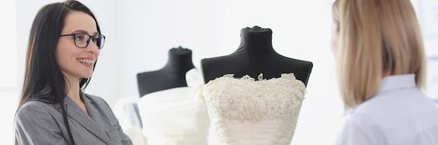 Consultora de mulher mostrando vestido de noiva para noiva em conceito de alfaiataria de salão de beleza