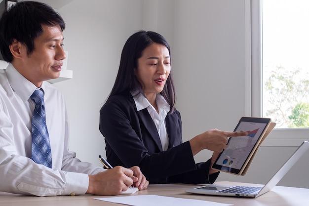 Consultora de negócios feminina explica gráfico de informações de ações para treinamento de negociação de ações para proprietários de negócios do sexo masculino que usa a negociação de ações ou crescimento de negócios de pme.