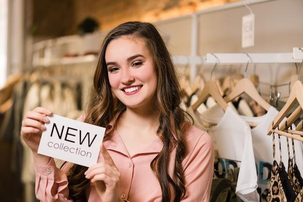 Consultora morena sorridente na loja com etiqueta nova coleção branca