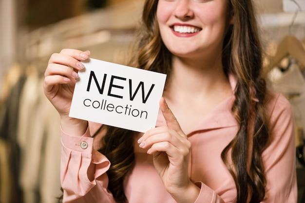 Consultora morena sorridente na loja com nova etiqueta de coleção