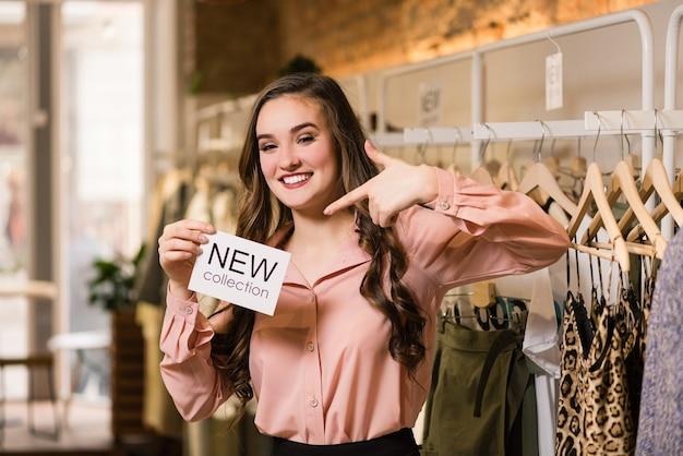 Consultora morena sorridente segurando etiqueta branca na loja