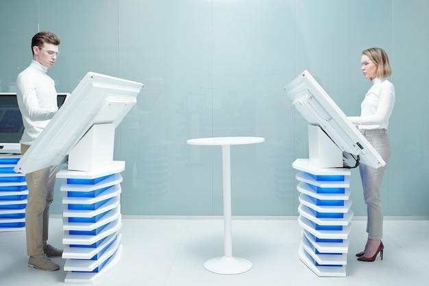 Consultores de centro móvel em gola alta branca em pé em monitores interativos e trabalhando com informações em um escritório moderno