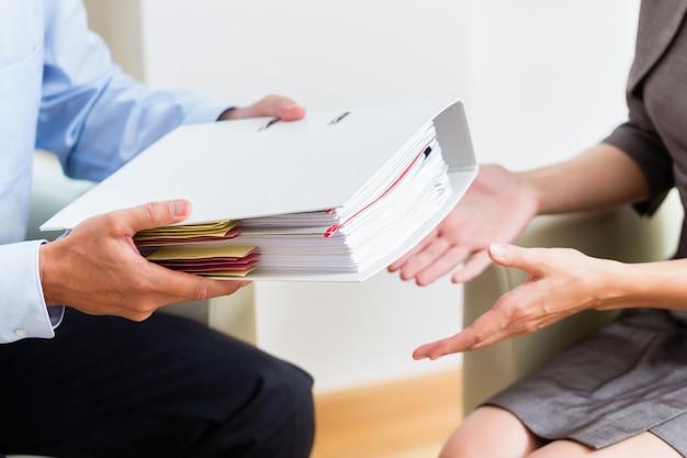 Consultoria financeira - cliente entregando documentos ao consultor para análise posterior