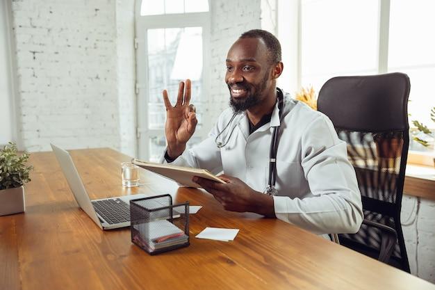 Consultoria médica para paciente, dando recomendação. médico afro-americano durante seu trabalho com pacientes, explicando receitas de remédios. trabalho árduo diário pela saúde e salvamento de vidas durante a epidemia.