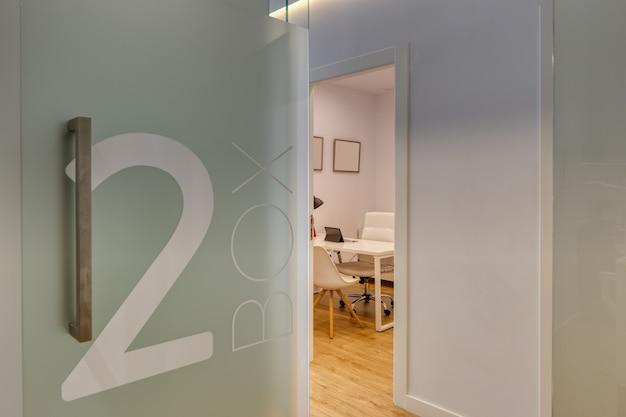 Consultório odontológico moderno e totalmente equipado, com telas de vidro, paredes brancas numeradas e piso de madeira.