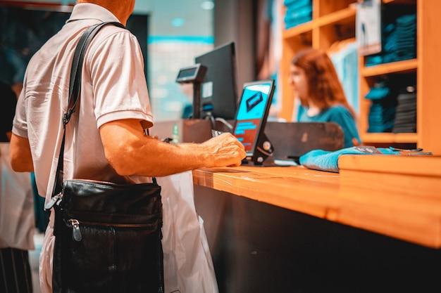 Consumidor adulto pagando com cartão de crédito na loja, segurando carteira
