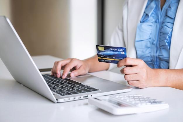 Consumidor de mulher de negócios, mantendo o cartão de crédito e digitando no laptop para compras e pagamentos on-line, faça uma compra na internet, pagamento on-line, redes e compre a tecnologia do produto