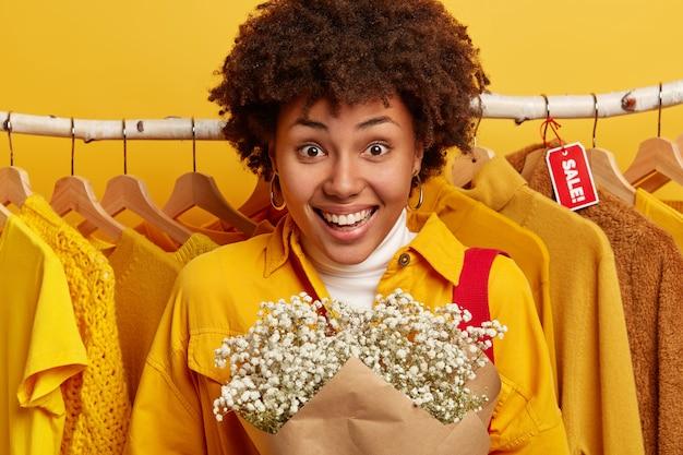 Consumidor de mulher encaracolada gosta de fazer compras, fica com buquê em boutique de moda.