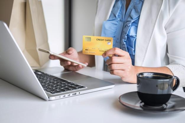 Consumidor jovem segurando smartphone, cartão de crédito e digitando no laptop para compras e pagamentos on-line, faça uma compra na internet, pagamento on-line, redes e compre a tecnologia do produto