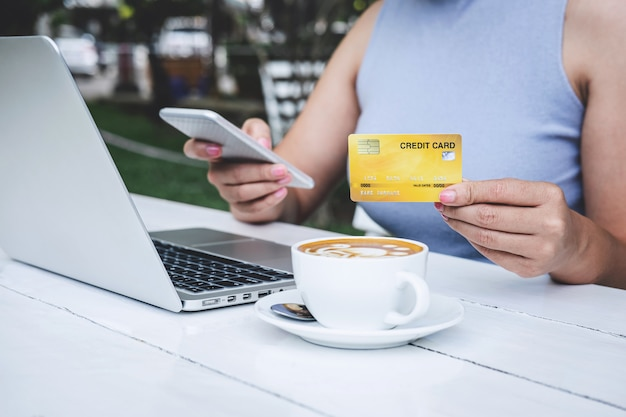 Consumidor, segurando, smartphone, cartão crédito, e, digitando, ligado, laptop, para, shopping online, e, pagamento