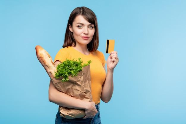 Consumidora muito jovem com uma sacola de papel contendo pão fresco e salsa verde mostrando seu cartão de crédito