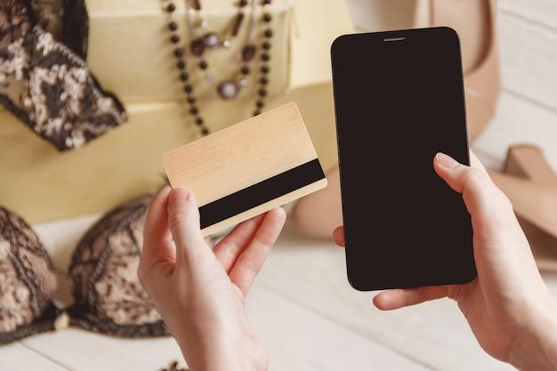 Consumismo e conceito de venda - close-up da mão feminina com cartão de crédito e smartphone