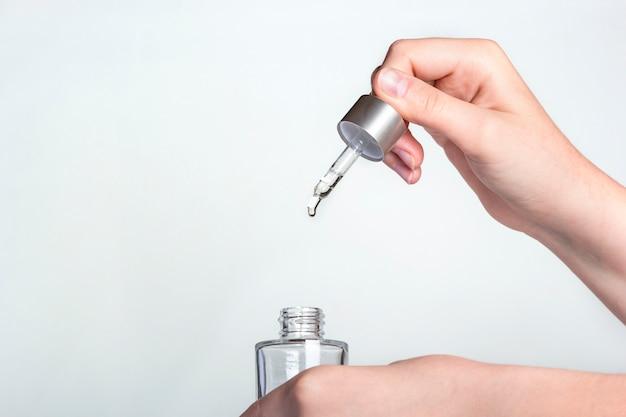 Conta-gotas com gota de óleo natural acima da garrafa de vidro